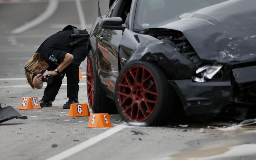 Irvine Police Department CSI Debra Werksman documents the scene of a fatal hit-and-run accident at the intersection of Muirlands Boulevard and Alton Parkway on the morning after Wednesday night's crash.