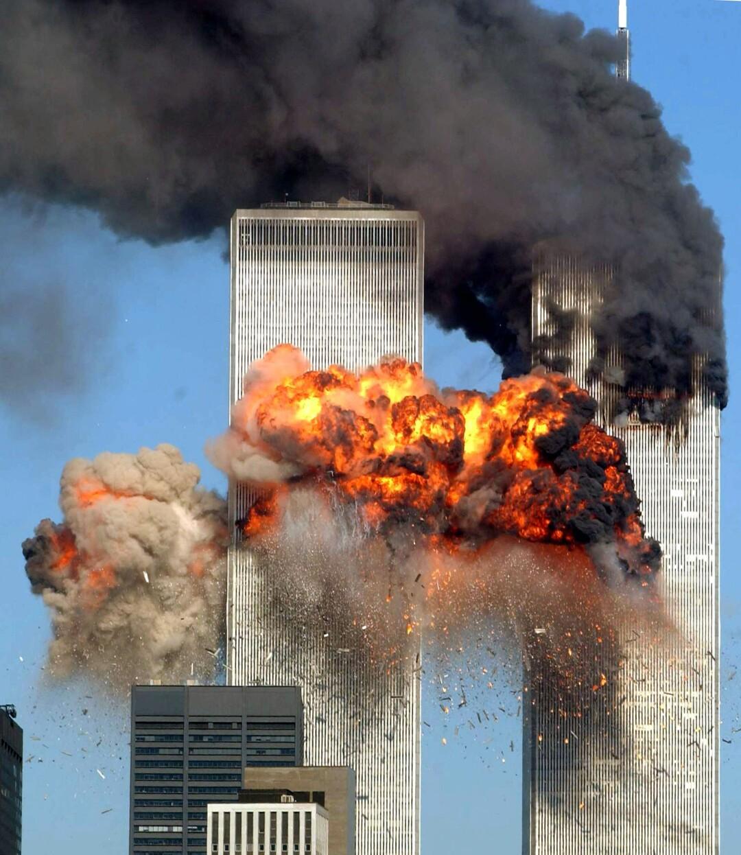 انفجاری از برج در سمت چپ و دود سیاه از برج در سمت راست می ریزد