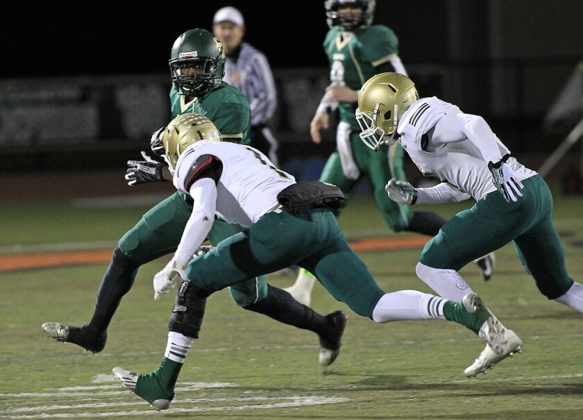 The Long Beach Poly defense pursues St. Bonaventure's Bryce Dixon during Pac-5 quarterfinal football playoff game last November.