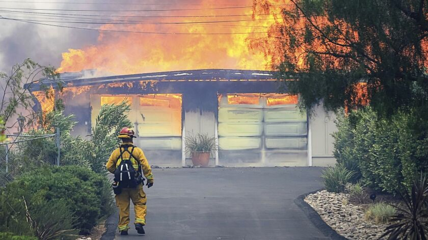 A firefighter approaches a burning home along Olive View Road during a wildfire in Alpine.