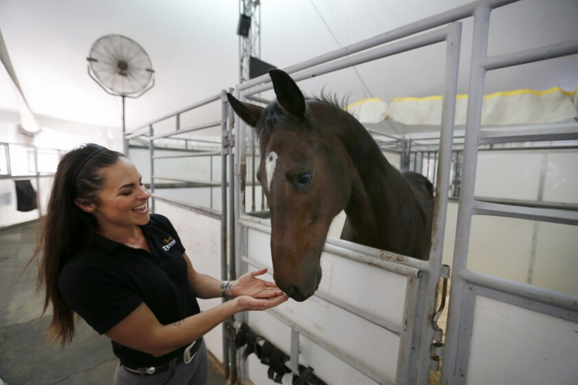 "Rebecca Ratte, a rider and aerialist, interacts with a horse before practice for the ""Odysseo"" by Cavalia show in Irvine."