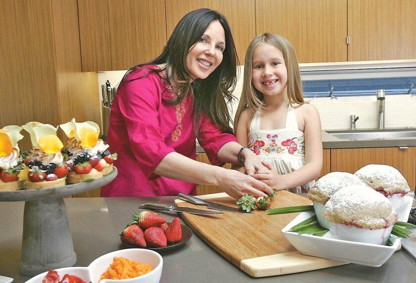 Karen Krasne and daughter Sahara Kiskis, 7, cut strawberries in their new kitchen.