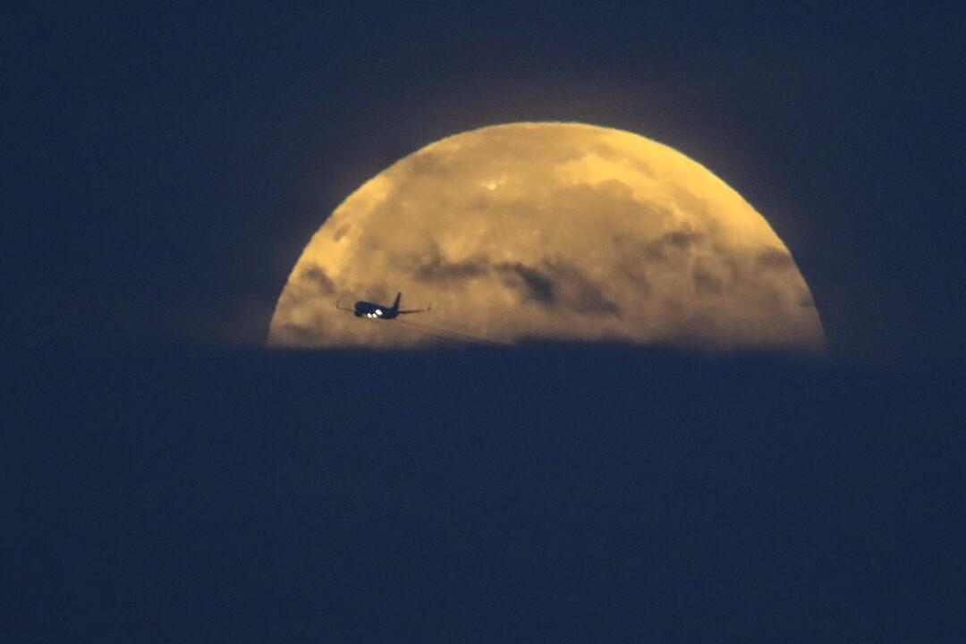 Un aeroplano attraversa davanti alla luna piena mentre tramonta
