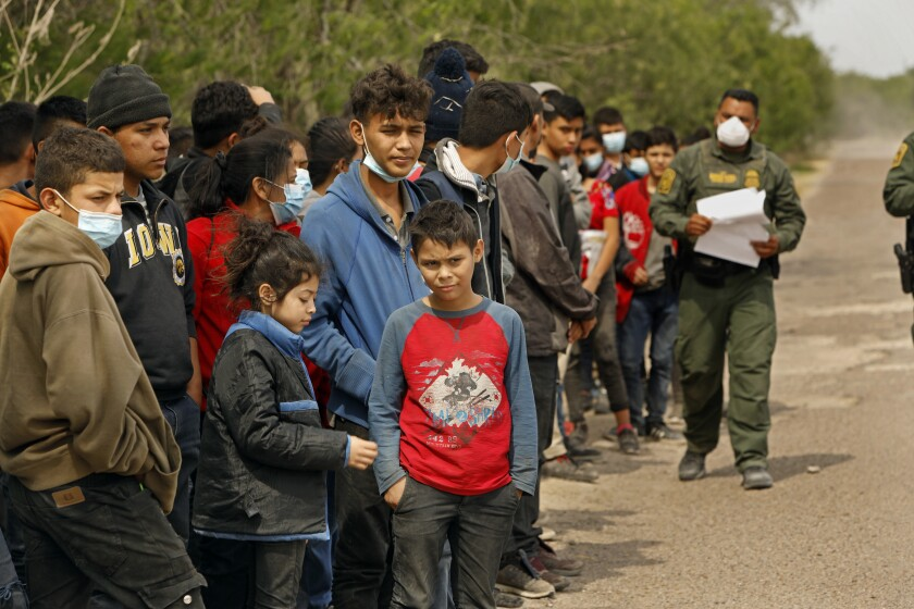 Young people stand outdoors in a line alongside a masked man in a uniform holding papers.