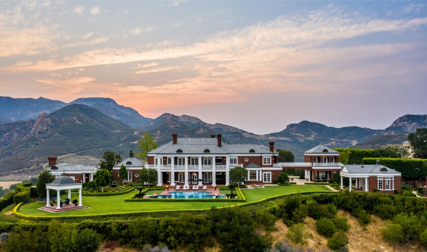 A red-brick Colonial-style estate with a massive green lawn and pool on a hilltop at sunset