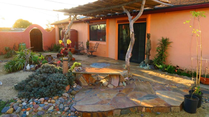 A Southwest-themed garden surrounds a Clairemont home on the community's 22nd annual tour. The pergola's tree trunk supports were salvaged after a fire at architect James Hubbell's Julian home.