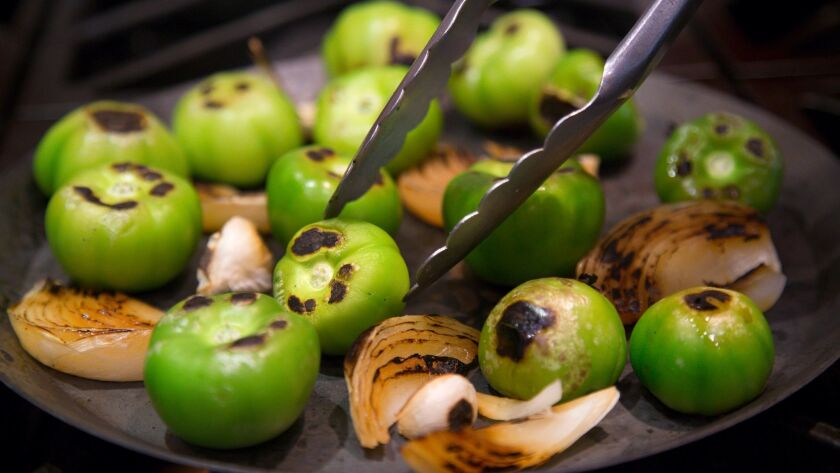 A comal, or griddle, is used to prepare roasted tomatillos and onions for a smoked tomatillo salsa.