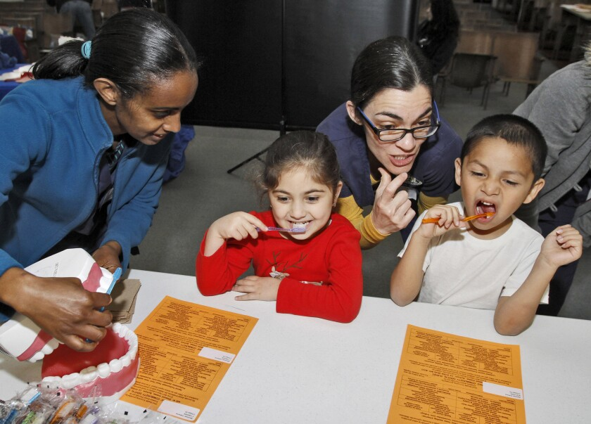 West L.A. College dental hygiene students Tirsit Belew, left, and Leanne Wright, right, show Joaquin Miller Elementary School students Catherine Mkrtchyan, left, and Anthony Sanchez, right, how to properly brush their teeth during the Kids' Community Dental Clinic at the Burbank school on Wednesday, Feb. 25, 2015. The free Give Kids A Smile event provided free dental check up for all the school's students.