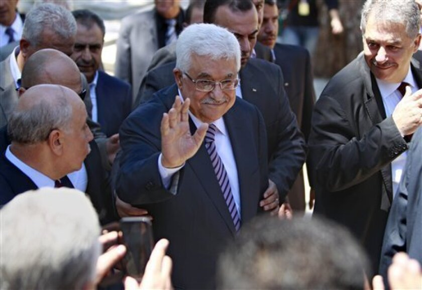 Palestinian President Mahmoud Abbas, center, waves during a visit to a Palestinian cemetery in Beirut, Lebanon, Friday, July 5, 2013. Abbas is in Beirut for three-day visit to meet with Lebanese officials. (AP Photo/Bilal Hussein)