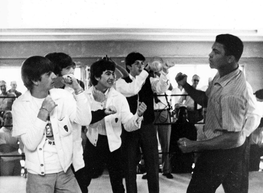 FILE - In this Feb. 18, 1964, file photo, the Beatles, from left, Ringo Starr, John Lennon, George Harrison, and Paul McCartney spar up to Muhammad Ali, or Cassius Clay at the time, while visiting the heavyweight contender at his training camp in Miami Beach, Fla.   Ali, the magnificent heavyweight
