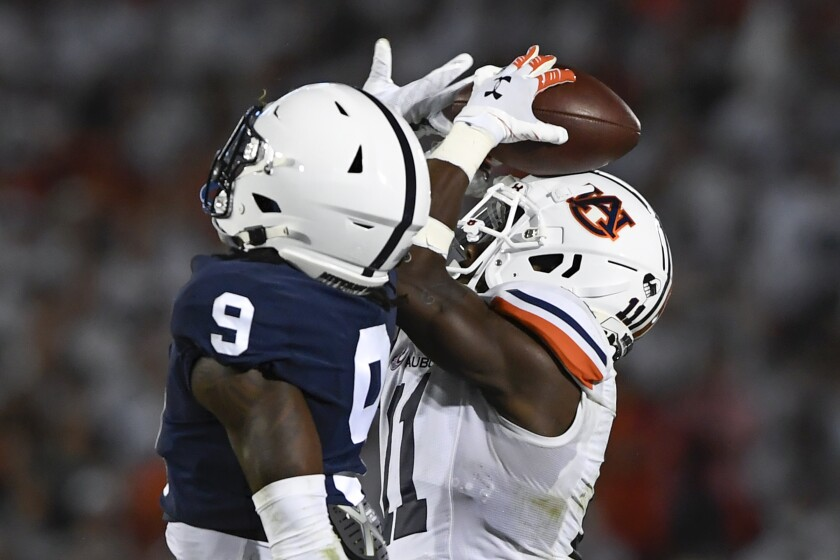Auburn wide receiver Shedrick Jackson (11) attempts to secure a catch against his helmet as Penn State cornerback Joey Porter Jr. (9) defends during the second half of an NCAA college football game in State College, Pa., Saturday, Sept.18, 2021. Penn State won 28-20. (AP Photo/Barry Reeger)