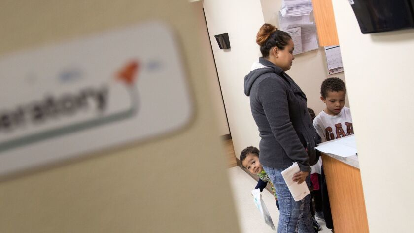 Josiya Grant, 2, left, peeks around mom Angel Grant as she and son Jakub, 8, complete paperwork after a dentist visit at the Antelope Valley Community Clinic.