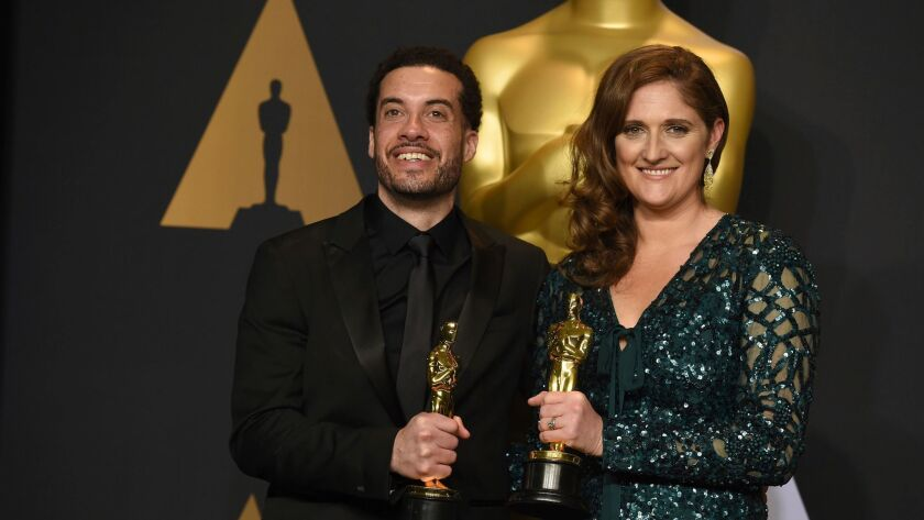 Ezra Edelman and Caroline Waterlow pose in the press room at the Oscars on Sunday. (Jordan Strauss / Invision/AP)