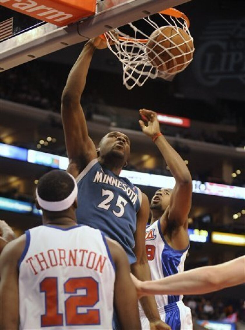 Minnesota Timberwolves' Al Jefferson, center, scores against the Los Angeles Clippers, including Al Thornton (12), during the first half of an NBA basketball game in Los Angeles on Monday, Jan. 19, 2009. (AP Photo/Phil McCarten)