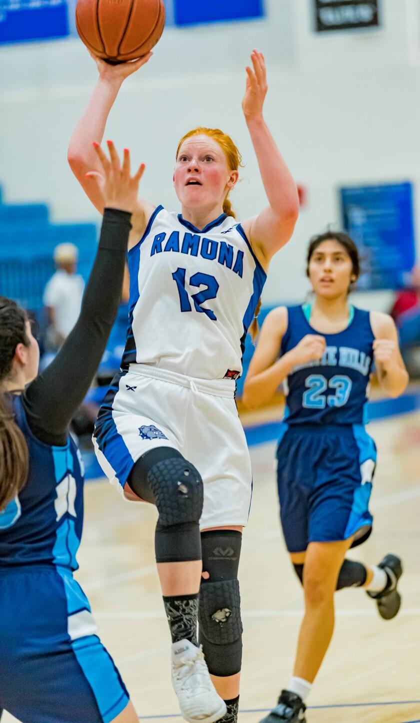Bulldogs girls basketball power forward Sarina Talle gets air for a shot.