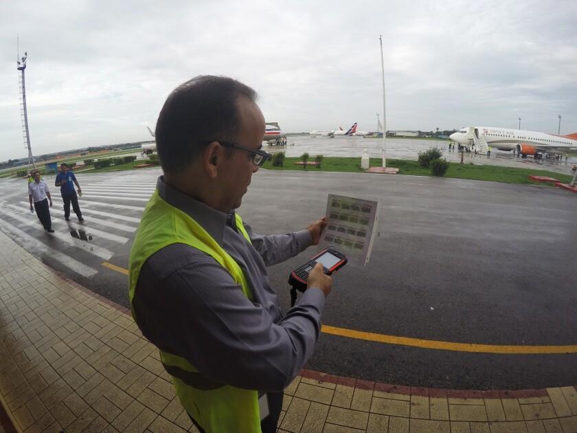Galo Beltrán, gerente de American Airlines en Cuba, ensaya un scanner de equipaje en el aeropuerto José Martí de La Habana. El Departamento de Transportes de EEUU dijo el viernes 10 de junio de 2016 que las aerolíneas American, Frontier, JetBlue, Silver Airways, Southwest y Sun Country han sido seleccionadas para operar rutas a nueve ciudades cubanas. (AP Foto/Scott Mayerowitz)