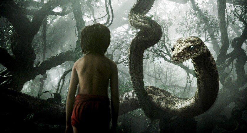 """Mowgli, played by newcomer Neel Sethi, meets Kaa the snake, voiced by Scarlett Johansson, in """"The Jungle Book."""""""