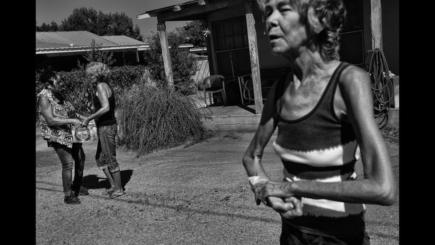Becky Keck, foreground, accepted bottled water from Donna Johnson, left. Donna Johnson realized that East Porterville was in big trouble when well after well in the parched town began to go dry. She decided to do something and now is busy each and every day delivering water.