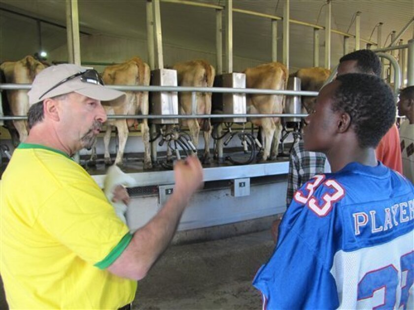 In this photo taken July 23, 2010, Frank Toledo, left, explains to Abdi Abdullahi, right, how cows at Threemile Canyon Farms are milked during a tour with new workers in Boardman, Ore. There is little the International Rescue Committee, an Idaho-based refugee agency, can do to prepare its Third Wor
