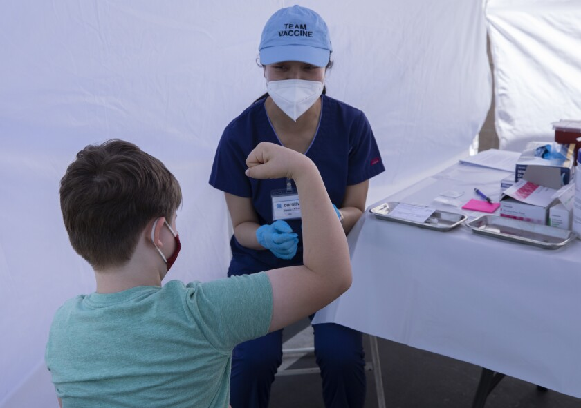 A boy flexes as a nurse stands next to him in a white medical tent