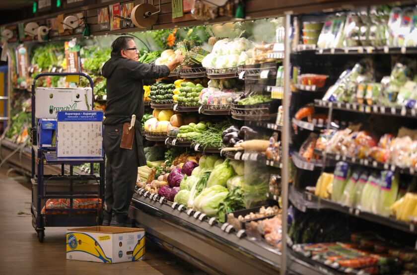 Victor Marcus, a produce clerk at the Ralphs supermarket in the La Jolla Square shopping center, restocks produce at the store, early in the morning, March 19, 2020 in San Diego, California.