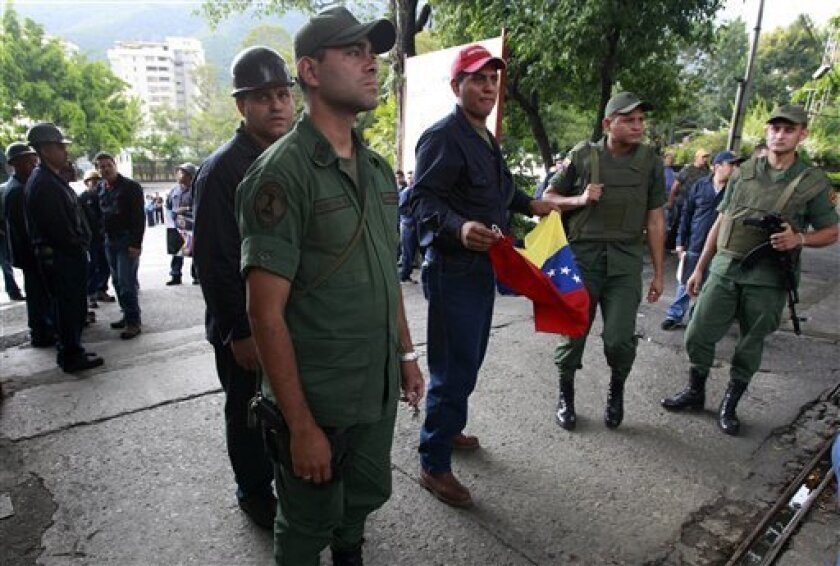 National Guard soldiers stand guard in a steel factory run by Sidetur, Siderurgica del Turbio SA, as a worker holds a Venezuelan flag in Caracas, Venezuela, Monday Nov. 1, 2010. Chavez ordered the expropriation of Venezuela's largest privately owned steel producer on Sunday, saying it is part of his strategy to transform Venezuela into a socialist state. (AP Photo/Fernando Vergara)