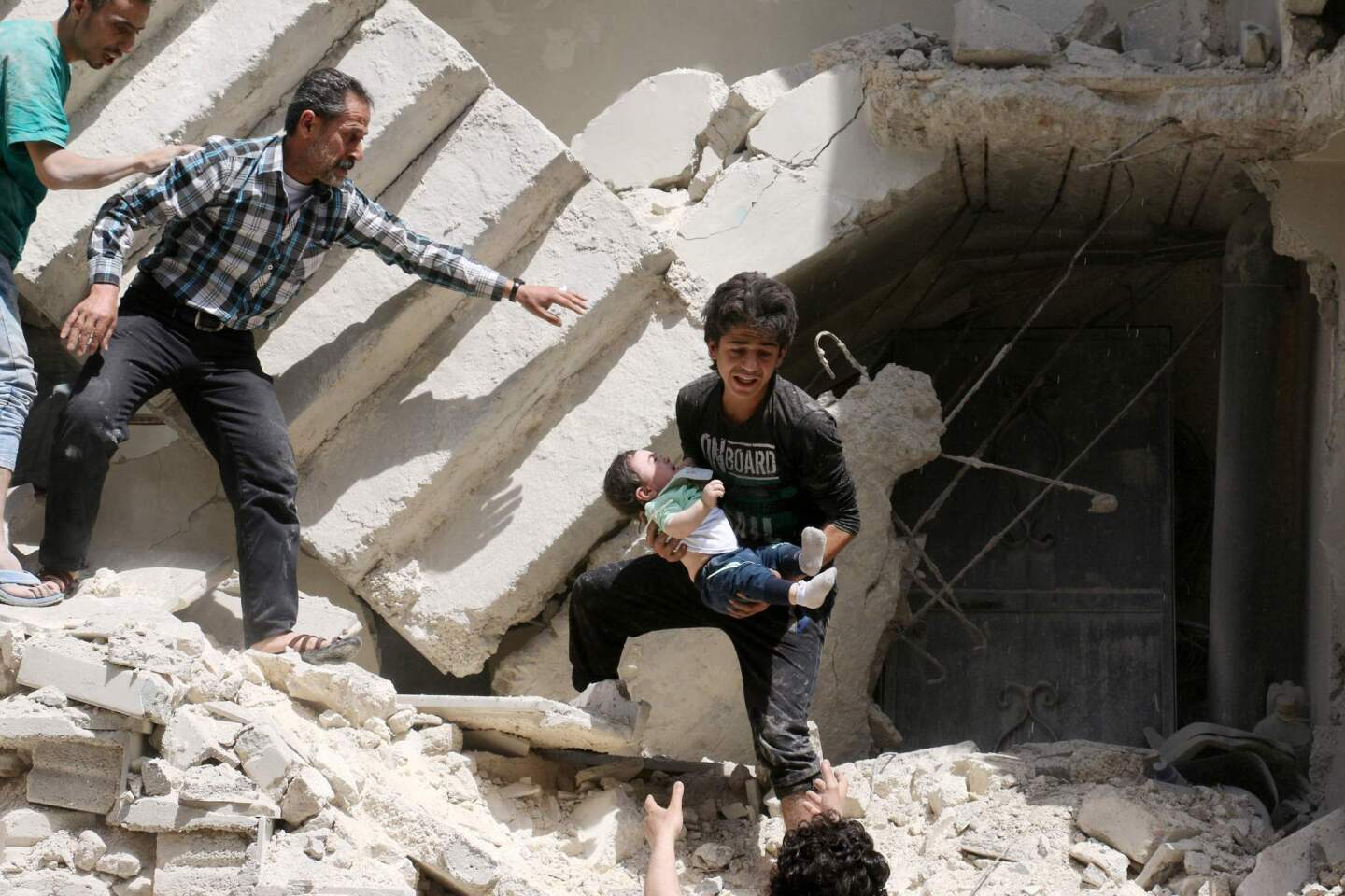 Syrians evacuate a toddler from a destroyed building after an airstrike on the rebel-held Kalasa neighborhood in the northern Syrian city of Aleppo.