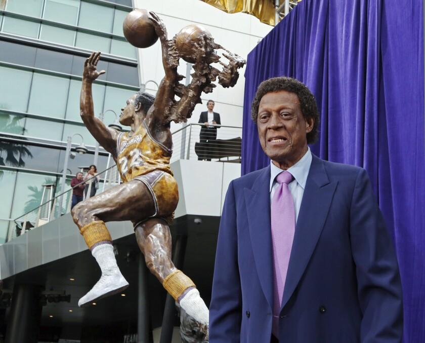 Elgin Baylor posa frente a una estatua en su honor frente a la arena Staples Center de Los Ángeles