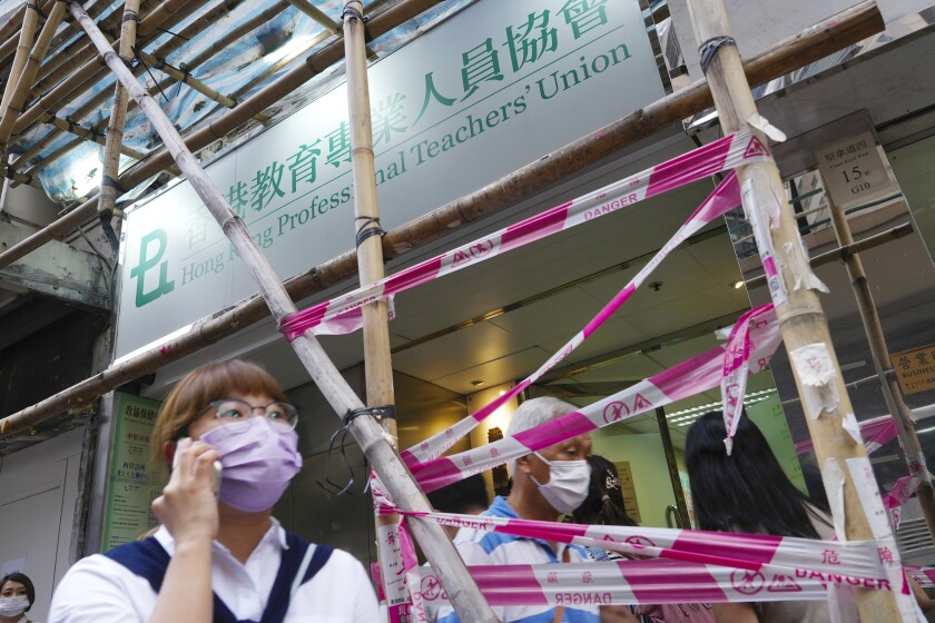 """People walk past the entrance of the Hong Kong Professional Teachers' Union in Hong Kong, Tuesday, Aug. 10, 2021. The pro-democracy Professional Teachers' Union, the city's largest single-industry trade union comprising of 95,000 members, said it had disbanded as the """"social and political environment has changed in recent years."""" (AP Photo/Vincent Yu)"""