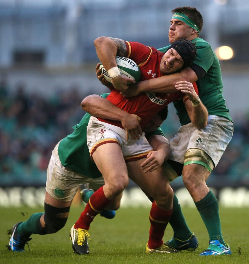 Wales' Tom James, centre, is caught by Ireland's CJ Stander, right, during the 2016 Six Nations rugby match at the Aviva Stadium in Dublin, Ireland, Sunday Feb. 7, 2016.  (Niall Carson / PA via AP) UNITED KINGDOM OUT - NO SALES - NO ARCHIVES