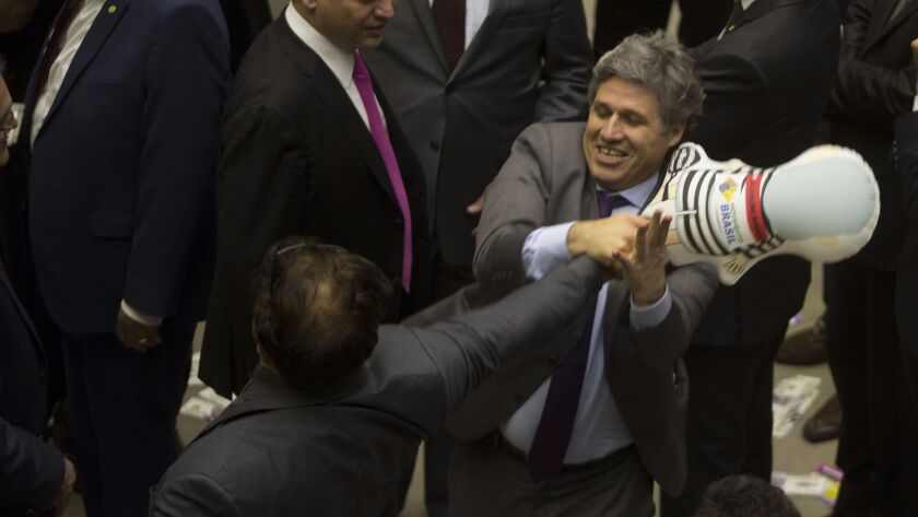 Paulo Teixeira, right, grabs an inflatable doll depicting former President Luiz Ignacio Lula da Silva from Wladimir Costa. They are members of Brazil's Chamber of Deputies, which debated the future of President Michel Temer.