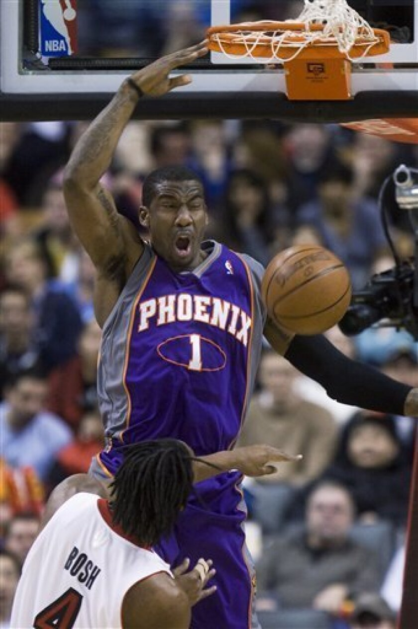 Toronto Raptors Chris Bosh, front, watches as Phoenix Suns forward Amar'e Stoudemire (1) dunks the ball during the first half of an NBA basketball game in Toronto on Sunday, Jan. 18, 2009. (AP Photo/The Canadian Press, Nathan Denette)