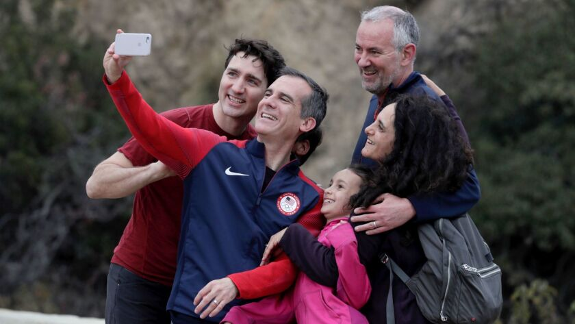 Canadian Prime Minister Justin Trudeau, left, and Mayor Eric Garcetti take a selfie with Greg and Al