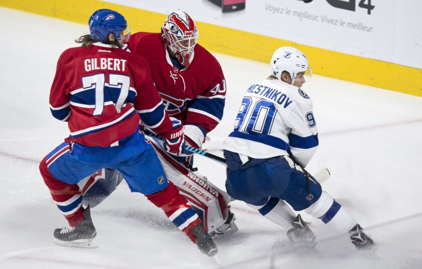 Montreal Canadiens goalie Ben Scrivens and defenseman Tom Gilbert knock the puck away from Tampa Bay Lightning's Vladislav Namestnikov during the first period of an NHL hockey game, Tuesday, Feb. 9, 2016, in Montreal.  (Paul Chiasson/The Canadian Press via AP) MANDATORY CREDIT
