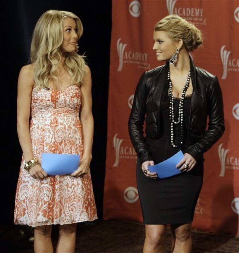Julianne Hough, left, reacts to hearing her name read as a nominee for top new female vocalist by the Academy of Country Music during a news conference in Nashville, Tenn., Wednesday, Feb. 11, 2009. The ACM awards show will be held April 5, 2009, in Las Vegas. Jessica Simpson is at right. (AP Photo/Mark Humphrey)