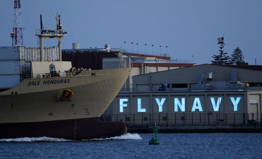 "A Dole ship moves by the ""Fly Navy"" sign that is illuminated at North Island Naval Air Station."