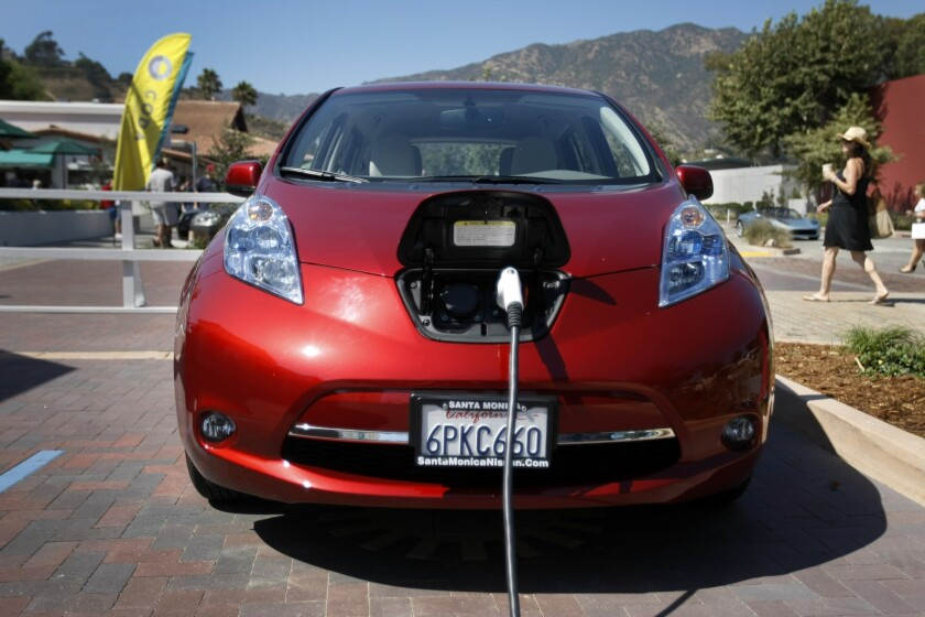 An electric Nissan Leaf is plugged in at a charging station in Malibu.