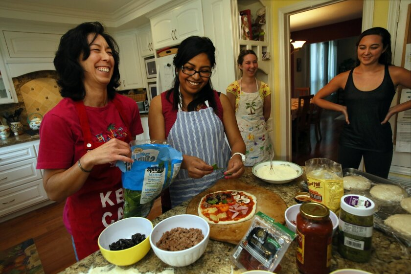 Valerie Wentworth, left, making pizza with Sandra Ramirez, 24, at Valerie's Scripps Ranch home. At right are Valerie's daughters Vanessa, 14, and Sabrina, 17.