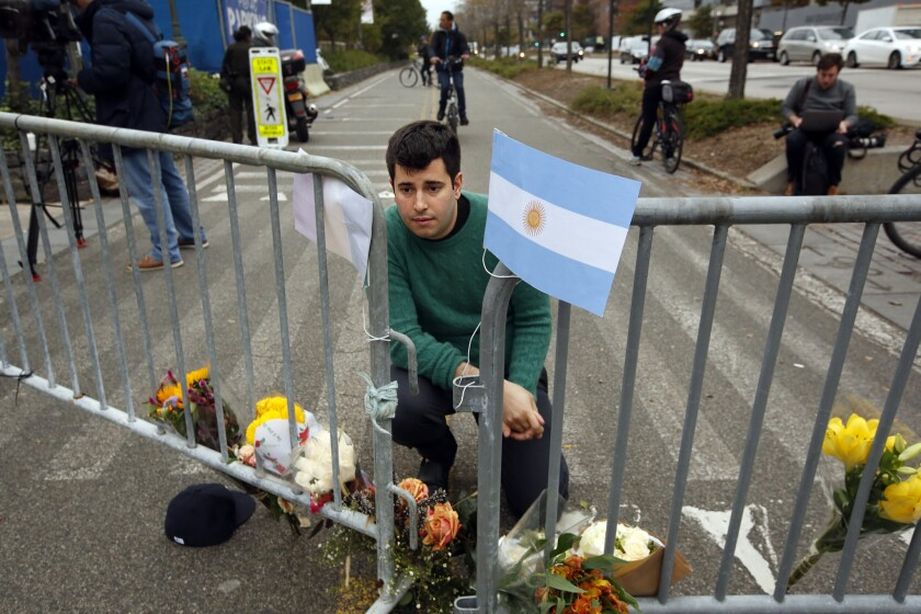 "George Embiricos, 27, leaves flowers on the bike path along West Street in Manhattan. ""I walk the path every day. It's been a source of peace for me. It's hard to see the city where I grew up like this,"" he said."