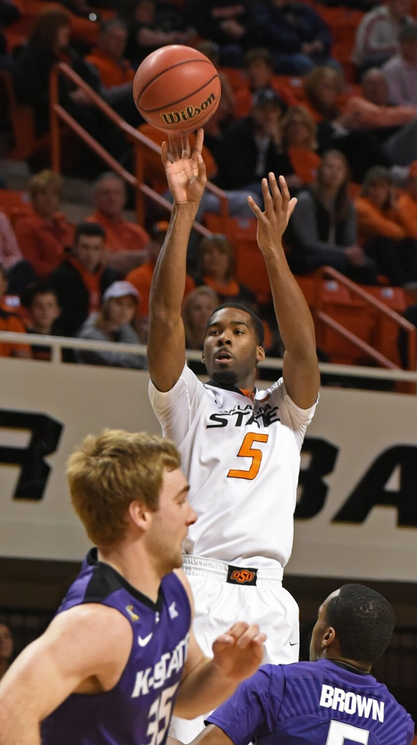 Oklahoma State guard Tavarius Shine, center, shoots over Kansas State forward Austin Budke, left, and guard Barry Brown in the first half of an NCAA college basketball game in Stillwater, Okla., Saturday, Feb. 13, 2016. Shine scored 11 points in their 58-55 win. (AP Photo/Brody Schmidt)