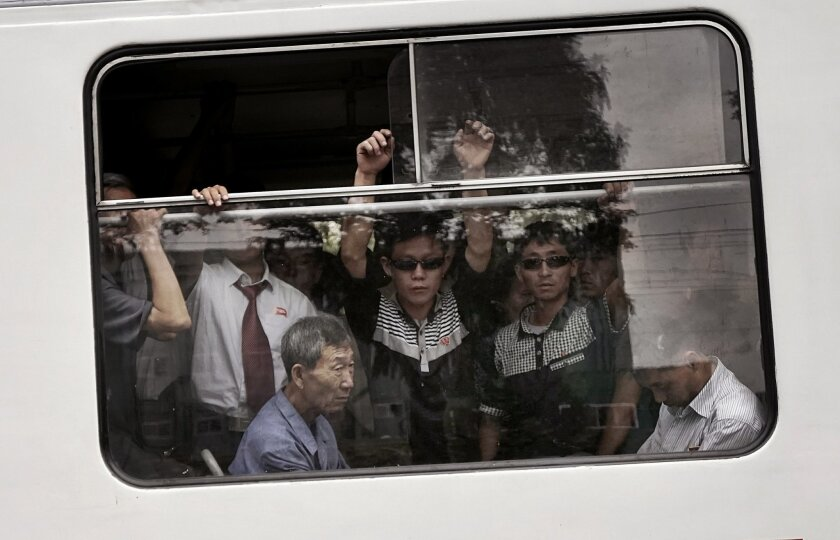 FILE - In this Sept. 11, 2015, file photo, commuters ride on a crowded city trolley bus, in Pyongyang, North Korea. Though dimly aware that more sanctions may be on the way because of the latest nuclear test and rocket launch, most North Koreans seem almost blase about it. Life is much tougher in t