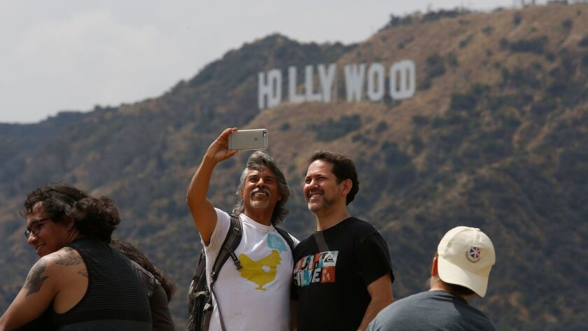 Hikers take a selfie with the Hollywood sign from the Tiffany & Co. Foundation Overlook in Los Angeles on May 15, 2016.