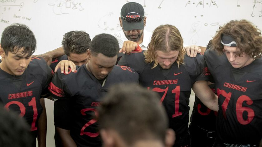 Former USC running backs coach Todd McNair prays with players before the game with his Village Christian Crusaders in Burbank on Friday.
