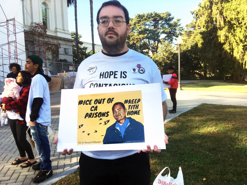 Connor Gorman of Davis, Calif., joins a rally on behalf of Cambodian refugee Tith Ton, who is awaiting parole from a murder conviction but could be deported to Cambodia, at the California Capitol in Sacramento, Calif., Friday, Nov. 1, 2019. Immigrant rights groups are calling on Gov. Gavin Newsom to end policies they say ease the transfer of prison inmates to federal authorities despite California's efforts to provide a sanctuary to those who are in the country illegally. (AP Photo/Don Thompson)