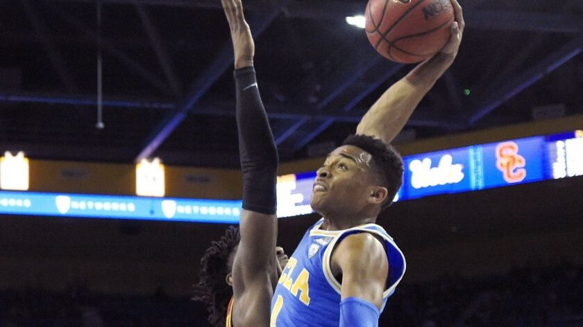 UCLA guard Jaylen Hands, right, goes up for a dunk as USC guard Jonah Mathews defends during the first half on Thursday, Feb. 28.