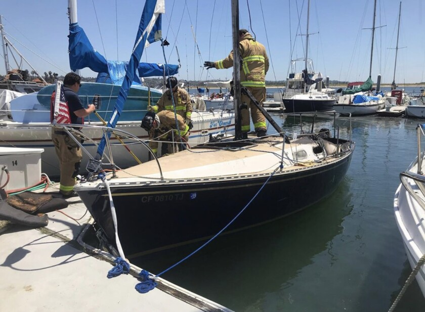 San Diego Fire-Rescue crews inspect a 22-foot boat after it caught fire Wednesday afternoon.