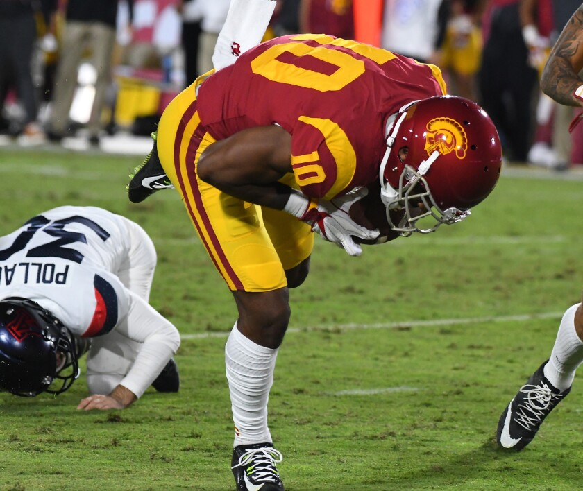 USC linebacker John Houston Jr. recovers a blocked put off kicker Josh Pollack and runs it into the end zone for a touchdown during the first quarter of a game at the Coliseum.