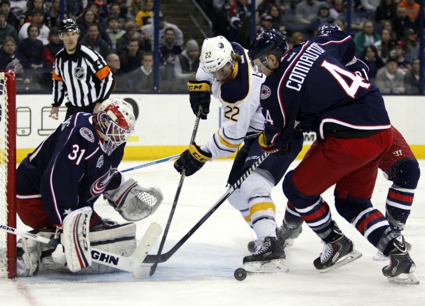 Buffalo Sabres' Johan Larsson (22), of Sweden, works for the puck between Columbus Blue Jackets goalie Anton Forsberg (31), of Sweden, and Kevin Connauton (4) during the first period of an NHL hockey game in Columbus, Ohio, Tuesday, Feb. 24, 2015. (AP Photo/Paul Vernon)