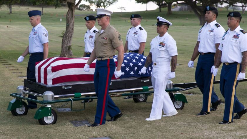 Pallbearers escort the remains of unidentified Oklahoma crew members that were exhumed in 2015 from the National Memorial Cemetery of the Pacific in Honolulu.