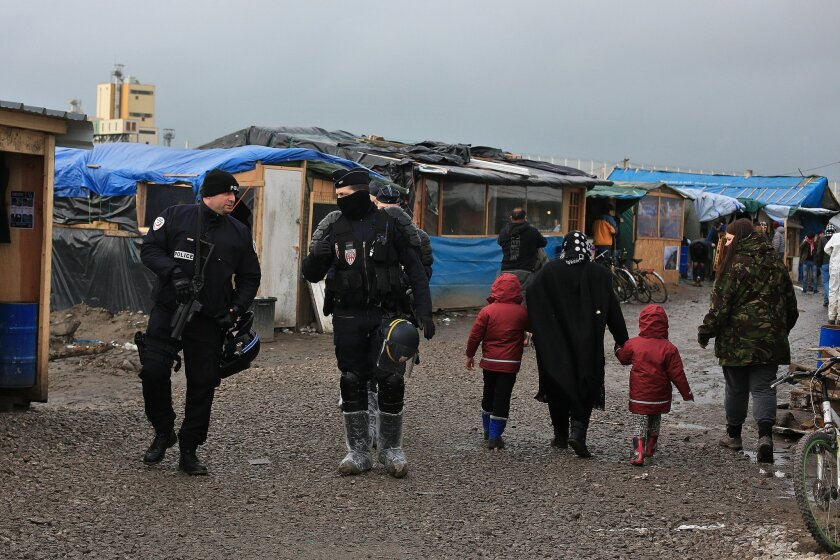 In this Feb. 5, 2016 photo, French riot police officers patrol in the migrant camp in Calais, north of France. Mysterious armed groups are on the prowl, targeting migrants in night attacks in Calais and other migrant haunts in northern France, sowing fear among the displaced travelers living in squ